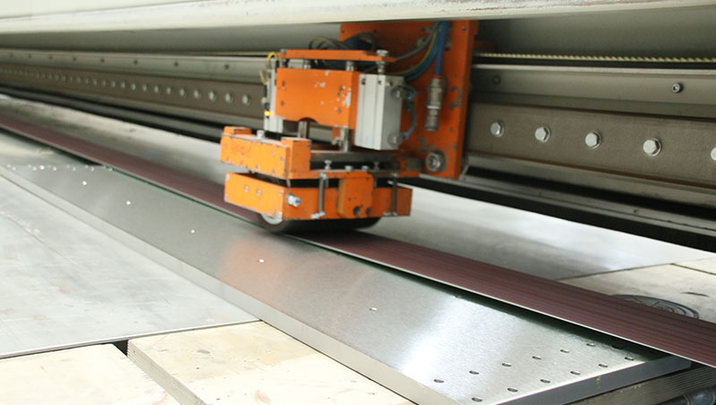Eine Edelstahlplatte wird mittels Langband-Schleiftechnik geschliffen.